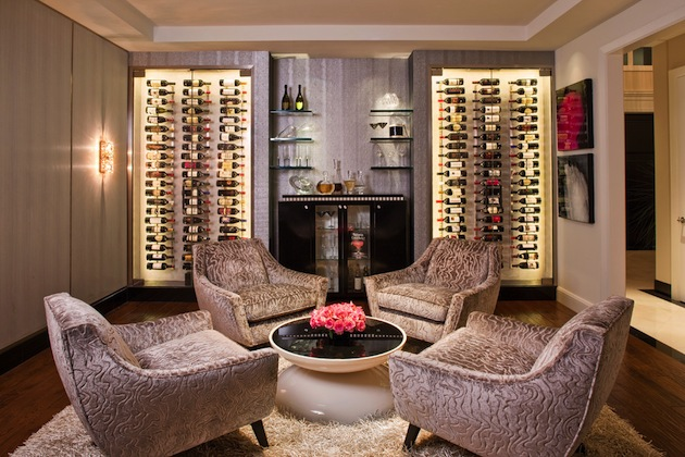 A sitting area with four armchair and coffee table and lots of wine bottles in two racks